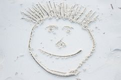 Funny smiley face drawn on white sand royalty free stock photo