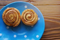 Homemade cinnamon rolls on a blue plate stand on a wooden table. Copy space for text. stock image