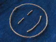 Funny smiley of twine in denim. Emoji sign handmade icon.  royalty free stock images