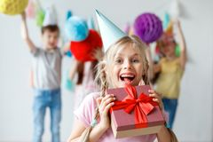 Funny smiling beautiful small child wears party hat, embraces big wrapped box, glad to recieve present from relatives Stock Photo