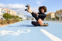 Funny smiling black girl sitting on bike line and puts on skates. Woman with afro hairstyle rollerblading on sunny day Stock Photos