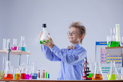 Funny smiling boy holding flask with reagent Royalty Free Stock Image