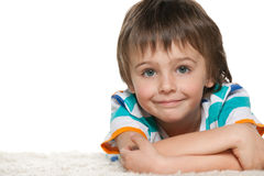 Funny smiling boy on the white carpet Stock Photo