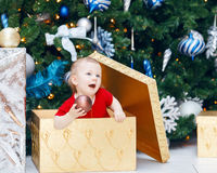 Funny smiling Caucasian baby girl toddler in red holiday dress sitting in large gift present box under New Year tree Stock Image