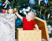 Funny smiling Caucasian baby girl toddler in red holiday dress sitting in large gift present box under New Year tree Royalty Free Stock Images