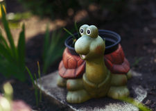 Funny smiling ceramic turtle in the garden. Funny ceramic turtle in garden, holding hotchpotch with plants royalty free stock photography