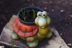 Funny smiling ceramic turtle in the garden. Funny ceramic turtle in garden, holding hotchpotch with plants stock photo