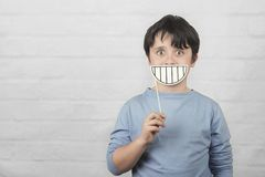 Funny and smiling child with a cardboard smile stock photos