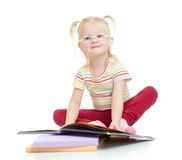 Funny smiling child in eyeglases reading book Stock Images