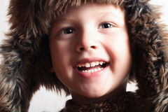 Funny smiling child in a fur hat. fashion kid. winter style. little boy. children Royalty Free Stock Photography