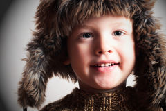 Funny smiling child in a fur hat. fashion kid. winter style. little boy. children Royalty Free Stock Images