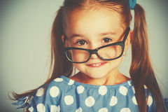 Funny smiling child girl in glasses. A funny smiling child girl in glasses stock photography