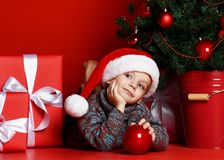 Funny smiling child in Santa red hat lying on on Christmas tree background royalty free stock images