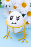 Funny smiling egg on stand and flowers for Easter, close-up Royalty Free Stock Photos