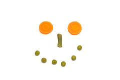 Funny smiling face. From carrots, beans and peas Royalty Free Stock Images