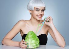 Funny smiling girl with cabbage cocktail on blue background. royalty free stock images