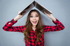 Funny smiling girl holding laptop above her head. Funny pretty smiling girl in plaid shirt holding laptop above her head Royalty Free Stock Photos