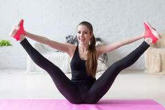 Funny smiling girl holding legs apart doing. Exercises aerobics warming up with gymnastics for flexibility leg stretching workout at home fitness royalty free stock images