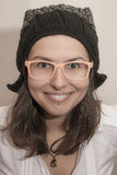 Funny smiling girl portrait with winter hat and summer glasses. Close-up portrait of young natural beauty girl with no make-up, looking happy and smiling. She is Royalty Free Stock Images