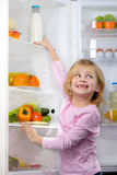 Funny smiling girl trying to pick food from fridge Royalty Free Stock Photography