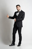 Funny smiling groom in tuxedo and bow tie showing thumbs up gesture Royalty Free Stock Photos