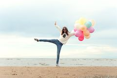 Funny smiling happy girl with many colored air balloons stock image