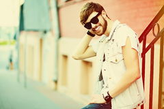 Funny smiling hipster handsome man in hipster cloth in the street Royalty Free Stock Image