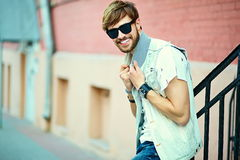 Funny smiling hipster handsome man in hipster cloth in the street Stock Photos