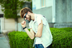 Funny smiling hipster handsome man in hipster cloth in the street Royalty Free Stock Images
