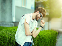 Funny smiling hipster handsome man in hipster cloth in the street Stock Image