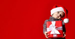 80d9ca7969057 Funny smiling child in Santa red hat holding Christmas gift in hand. royalty  free stock