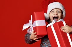 Funny smiling child in Santa red hat holding Christmas gift in hand. royalty free stock images