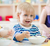 Funny smiling kid eating from plate in kindergarten stock photography