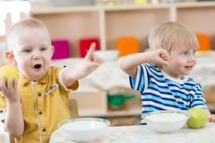 Funny smiling kids feeding in kindergarten stock photo