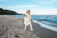 Funny smiling laughing white Caucasian child kid baby girl in fur coat and tutu skirt running on ocean sea beach on sunset Royalty Free Stock Photography