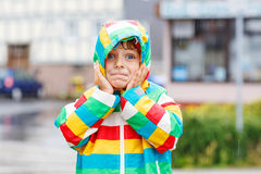 Funny smiling little boy walking in city through rain Royalty Free Stock Photography