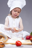 Funny Smiling Little Caucasian Girl In Cook Uniform Making a Mix of Flour, Eggs and Vegetables. Food Concepts and Ideas. Funny Smiling Little Caucasian Girl In Royalty Free Stock Image