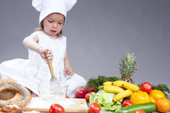 Funny Smiling Little Caucasian Girl In Cook Uniform Making a Mix of Flour, Eggs and Vegetables. Food Concepts and Ideas. Funny Smiling Little Caucasian Girl In Stock Photos