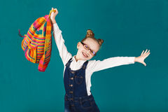 Funny smiling little girl with big backpack jumping and having f Stock Photography