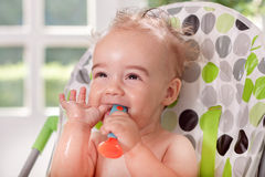 Funny smiling ragged baby holding spoon in mouth Stock Photography