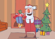 Funny smiling Santa Claus brings colorful boxes of gifts. Christmas decorated room with fireplace, stockings and. Funny smiling Santa Claus brings gifts in Royalty Free Stock Photo
