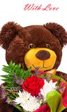 Funny smiling teddy bear with a bouquet of flowers Stock Image