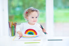 Funny smiling toddler girl drawing a rainbow Stock Image