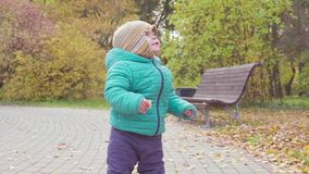 Funny smiling 1 year old boy Walking in the autumn Park at the Sunset with bread in hand . Happy Childhood Concept. Slow stock video footage