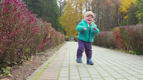 Funny smiling 1 year old boy Walking in the autumn Park at the Sunset with bread in hand . Happy Childhood Concept. Slow stock video