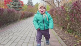 Funny smiling 1 year old boy Walking in the autumn Park at the Sunset with bread in hand . Happy Childhood Concept. Slow. Funny Little 1 year old boy Walking in stock video