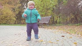 Funny smiling 1 year old boy Walking in the Park at the Sunset with bread in hand . Happy Childhood Concept. Slow motion stock video footage
