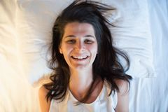 Funny smiling young woman on the white bed. View from above. Funny smiling young woman on the white bedroom bed. View from above Royalty Free Stock Photo