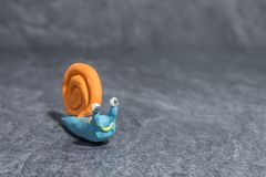 Funny snail made of play dough in front of grey background royalty free stock photo