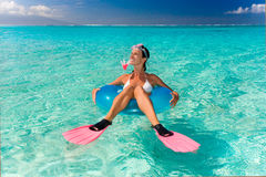 Funny snorkel woman. Beautiful woman on inflatable tube in turquoise waters Royalty Free Stock Photo